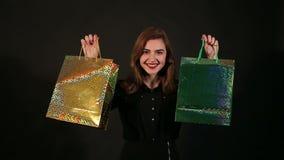 Portret van een modieus meisje met zakken in haar handen op een zwarte achtergrond Het winkelen stock footage