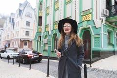 Portret van een modieus positief meisje dat op de achtergrond van mooie architectuur zet en aan muziek luistert stock afbeelding