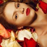 Portret van een modieus roodharig model in roze bloemblaadjes royalty-vrije stock foto's