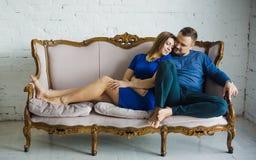 Portret van een modieuze modieuze paarzitting samen met naakte voeten op de laag in de woonkamer, het omhelzen, die glimlachen, royalty-vrije stock foto