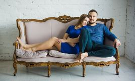 Portret van een modieuze modieuze paarzitting samen met naakte voeten op de laag in de woonkamer, het omhelzen, die glimlachen, stock afbeelding