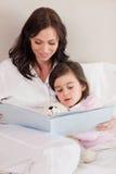 Portret van een moeder die een verhaal lezen aan haar dochter stock fotografie