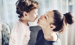 Portret van een moeder die haar geliefd kind kussen Stock Afbeeldingen