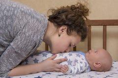 Portret van een moeder die zacht haar pasgeboren baby kust, die in bed ligt stock foto