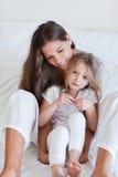 Portret van een moeder en haar dochter het stellen op een bed Royalty-vrije Stock Fotografie