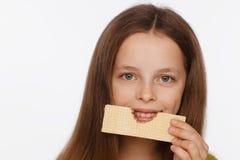 Portret van een mooi 8 ??njarigenmeisje in een sweater en met een wafeltje in haar hand Witte achtergrond royalty-vrije stock foto's