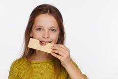 Portret van een mooi 8 ??njarigenmeisje in een sweater en met een wafeltje in haar hand Witte achtergrond stock fotografie