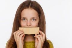 Portret van een mooi 8 ??njarigenmeisje in een sweater en met een wafeltje in haar handen Witte achtergrond royalty-vrije stock foto