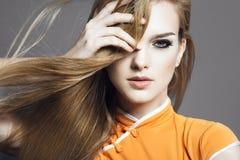 Portret van een mooi blondemeisje in de studio op een grijze achtergrond met het ontwikkelen van haar, het concept gezondheid en  Stock Afbeelding