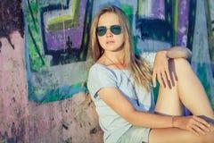 Portret van een mooi blondemeisje dichtbij de muur Royalty-vrije Stock Foto's