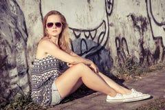 Portret van een mooi blondemeisje dichtbij de muur Royalty-vrije Stock Fotografie