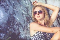 Portret van een mooi blondemeisje dichtbij de muur Stock Afbeelding