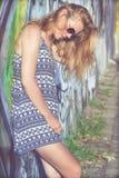 Portret van een mooi blondemeisje dichtbij de muur Stock Foto's