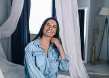 Portret van een mooi brunette dat op het bed in een witte slaapkamer zit royalty-vrije stock foto's