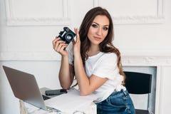 Portret van een mooi donkerharige die een camera, het glimlachen houden Zij is gekleed in moderne vrijetijdskleding, gebruikt stock afbeelding