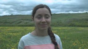 Portret van een mooi glimlachend meisje in een gebied en dichte wolken Gelukkige jonge vrouw op een gebied met gele bloemen en stock footage
