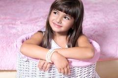 Portret van een mooi glimlachend meisje in een roze ruimte stock fotografie