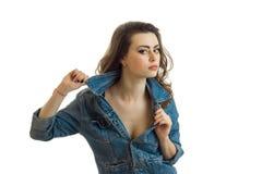Portret van een mooi jong brunette in jeansjasje dat net eruit ziet en handkraag houdt Royalty-vrije Stock Fotografie