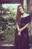 Portret van een mooi jong droevig gothmeisje in verlaten oud Stock Foto