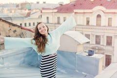 Portret van een mooi jong meisje dat in de avond op de daken van de oude stad loopt het concept vrijheid Zij bevindt zich met royalty-vrije stock fotografie