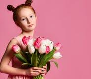Portret van een mooi jong meisje die in kleding groot die boeket van irissen en tulpen houden over roze achtergrond worden geïsol stock afbeelding