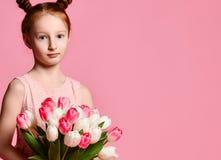 Portret van een mooi jong meisje die in kleding groot die boeket van irissen en tulpen houden over roze achtergrond worden geïsol royalty-vrije stock afbeeldingen