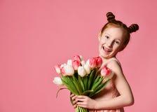 Portret van een mooi jong meisje die in kleding groot die boeket van irissen en tulpen houden over roze achtergrond worden geïsol royalty-vrije stock foto