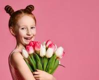 Portret van een mooi jong meisje die in kleding groot die boeket van irissen en tulpen houden over roze achtergrond worden ge?sol stock afbeeldingen