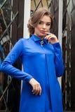 Portret van een mooi jong meisje in een blauwe kleding op een backgrou Stock Afbeeldingen