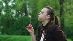 Portret van een mooi jong meisje in een bruin jasje die op een paardebloem blazen Jonge volwassenen stock video