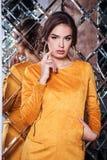 Portret van een mooi jong meisje in een gele kleding op een backgr Royalty-vrije Stock Afbeelding