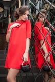 Portret van een mooi jong meisje in een rode kleding op een backgroun Royalty-vrije Stock Afbeeldingen