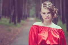 Portret van een mooi jong meisje in een rode kleding in openlucht Royalty-vrije Stock Afbeelding