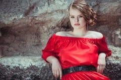 Portret van een mooi jong meisje in een rode kleding in openlucht Royalty-vrije Stock Afbeeldingen