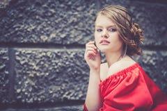 Portret van een mooi jong meisje in een rode kleding in openlucht Royalty-vrije Stock Fotografie