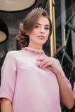 Portret van een mooi jong meisje in een roze kleding op een backgrou Stock Afbeelding