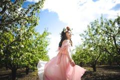 Portret van een mooi jong meisje in een vliegende bruid tedere roze kleding op een achtergrond van groen gebied, lacht zij en ste Stock Fotografie