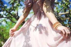 Portret van een mooi jong meisje in een vliegende bruid tedere roze kleding op een achtergrond van groen gebied, lacht zij en ste Royalty-vrije Stock Foto