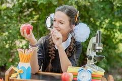 Portret van een mooi jong Schoolmeisje die door een vergrootglas kijken en bij een bureau zitten Stock Foto