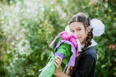 Portret van een mooi jong schoolmeisje met rode appel op boeken in een feestelijke eenvormige school Stock Fotografie