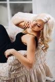 Portret van een mooi jong sexy blondemeisje met luxueus lang krullend haar in een elegante avondjurk met een zwarte Royalty-vrije Stock Foto's