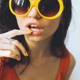 Portret van een mooi jong sexy donkerbruin meisje met expressieve ogen en volledige lippen, en zonnebril die voor de camera stell Stock Foto