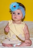 Portret van een mooi klein babymeisje in een gele kleding met een boog op haar hoofd dat parelsjuwelen rond zijn hals speelt Stock Foto