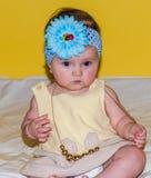 Portret van een mooi klein babymeisje in een gele kleding met een boog op haar hoofd dat parelsjuwelen rond zijn hals speelt Stock Afbeeldingen