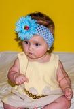 Portret van een mooi klein babymeisje in een gele kleding met een boog op haar hoofd en juwelenparels rond zijn hals Stock Fotografie