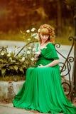 Portret van een mooi krullend haired zwanger meisje in groen Dr. royalty-vrije stock afbeelding