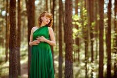 Portret van een mooi krullend haired zwanger meisje met haar ogen stock foto