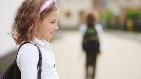Portret van een mooi krullend schoolmeisje Het meisje zegt vaarwel aan de jongen, de klasgenoot, de golven aan hem en de bladeren stock videobeelden