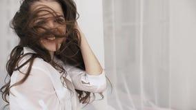 Portret van een mooi langharig brunette met haar die zich op die een wind ontwikkelen op een grijze achtergrond wordt geïsoleerd stock video