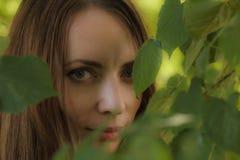 Portret van een mooi meisje in een boomgebladerte royalty-vrije stock afbeeldingen